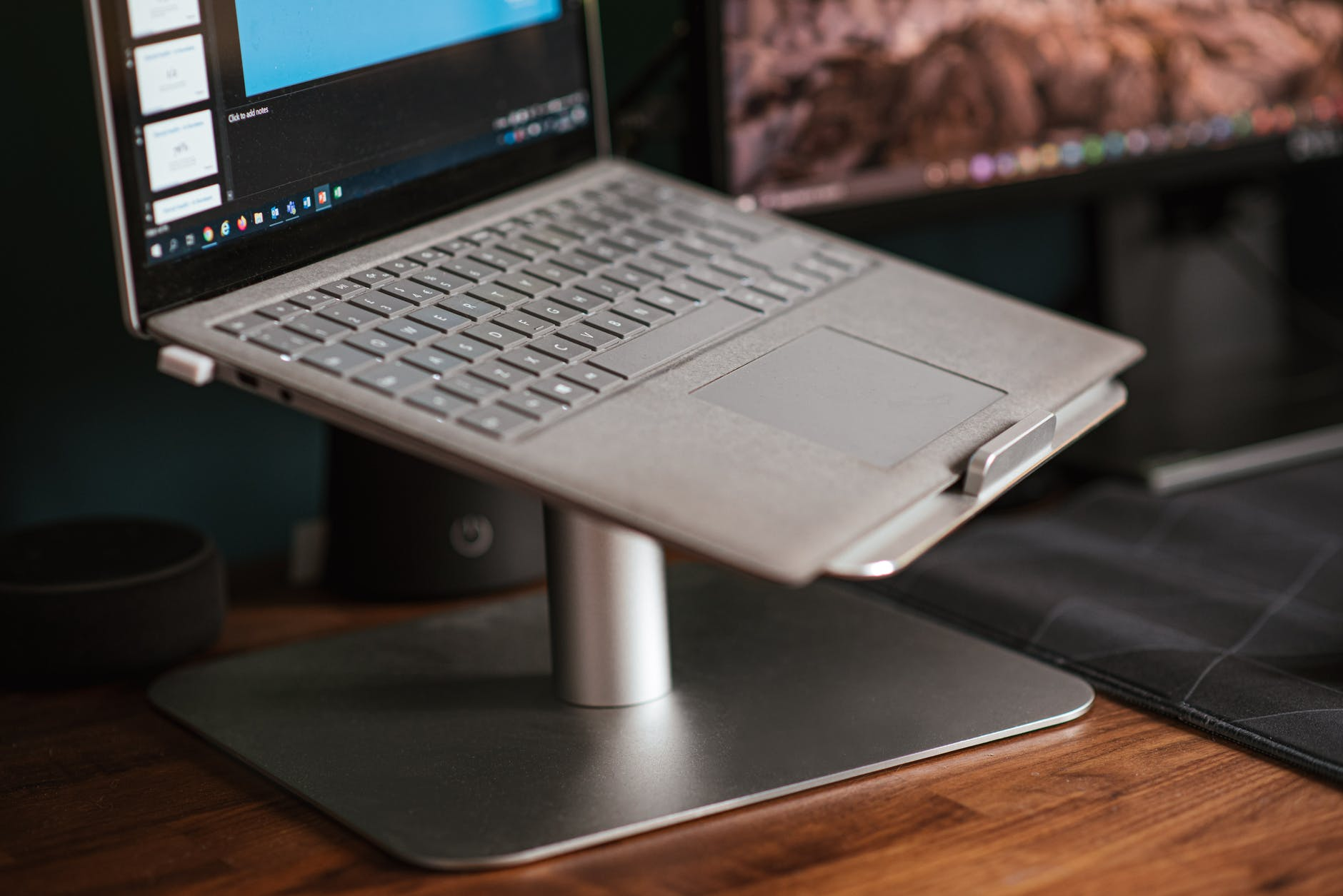modern laptop placed on stand on desk